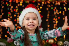 Child girl portrait in christmas decoration, happy emotions, winter holiday concept, dark background with illumination and boke li Stock Photos