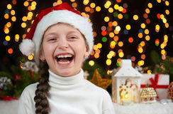 Child girl portrait on dark background with christmas decoration, face expression and happy emotions, dressed in santa hat, winter Stock Image
