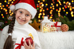 Child girl portrait on dark background with christmas decoration, face expression and happy emotions, dressed in santa hat, winter. Holiday concept stock photo