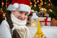 Child girl portrait with eiffel tower and christmas decoration, dark background with lights, face expression and happy emotions, d. Ressed in santa hat, winter royalty free stock photo