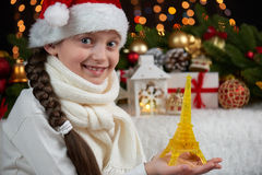Child girl portrait with eiffel tower figurine and christmas decoration, dark background with lights, face expression and happy em. Otions, dressed in santa hat stock image