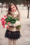 Child girl portrait with flowers on cozy warm outdoor winter walk Stock Photo