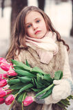 Child girl portrait with flowers on cozy warm outdoor winter walk Royalty Free Stock Photography