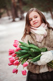 Child girl portrait with flowers on cozy warm outdoor winter walk Royalty Free Stock Images