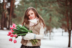 Child girl portrait with flowers on cozy warm outdoor winter walk Royalty Free Stock Photo