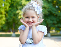 Child girl portrait, posing in white gown, face closeup, happy childhood concept, summer season in city park Royalty Free Stock Photos