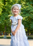Child girl portrait, posing in white gown, happy childhood concept, summer season in city park Royalty Free Stock Photography