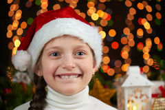 Child girl portrait in santa hat with christmas decoration, dark background with lights, face expression and happy emotions, winte Stock Images
