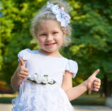 Child girl portrait in white gown show best gesture, happy childhood concept, summer season in city park Royalty Free Stock Image