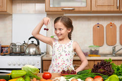 Child girl posing with cherry, fruits and vegetables in home kit Royalty Free Stock Photography