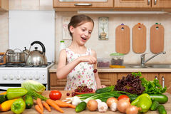 Child girl posing with cherry, fruits and vegetables in home kitchen interior, healthy food concept Royalty Free Stock Image