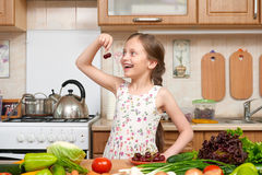 Child girl posing with cherry, fruits and vegetables in home kitchen interior, healthy food concept Stock Photos