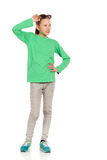 Child Girl Posing With Hand On Hip And Looking Away. Cheerful ten years old girl in green blouse, jeans and holding hand on hip and looking away. Full length Royalty Free Stock Photos