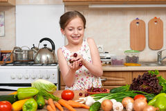 Child girl posing with handful of cherries, fruits and vegetable Royalty Free Stock Photography