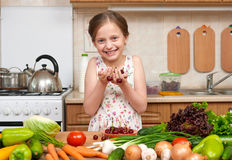Child girl posing with handful of cherries, fruits and vegetable Royalty Free Stock Image