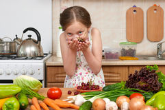 Child girl posing with handful of cherries, fruits and vegetable Stock Images