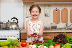 Child girl posing with handful of cherries, fruits and vegetables in home kitchen interior, healthy food concept Royalty Free Stock Image