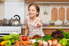 Child girl posing with handful of cherries, fruits and vegetables in home kitchen interior, healthy food concept Royalty Free Stock Photography