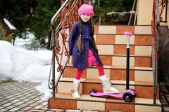 Child girl posing with scooter on house steps Royalty Free Stock Image