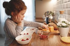 Child   preparing breakfast porridge with berries at home in mor Royalty Free Stock Image