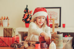 Child girl preparing gifts for christmas at home, cozy holiday interior Royalty Free Stock Photography