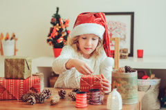Child girl preparing gifts for christmas at home, cozy holiday interior. Cute child girl in red santa hat preparing gifts for christmas at home, cozy holiday Royalty Free Stock Photography