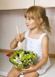 Child girl preparing salad. Little girl preparing and eating vegetable salad Royalty Free Stock Photos