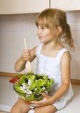 Child girl preparing salad. Little girl preparing and eating vegetable salad Royalty Free Stock Photos