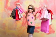 Child girl with present pack on colorful background. Small girl with shopping bag. Christmas and birthday. Holiday celebration and party. Childhood and Royalty Free Stock Photography