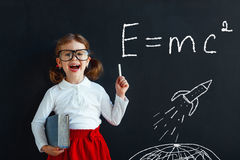 Child girl prodigy student with book near blackboard Royalty Free Stock Images