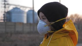 Child girl in protective mask on industrial plant smoke background. Atmospheric pollution and people health concept.