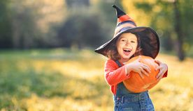Child girl with pumpkin outdoors in halloween Royalty Free Stock Photos