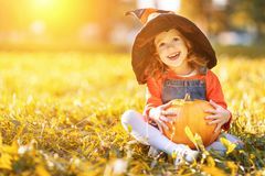 Child girl with pumpkin outdoors in Halloween Stock Photos