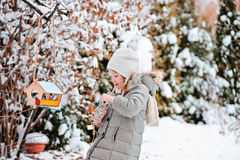 Child girl puts seeds in bird feeder in winter snowy garden Stock Photos