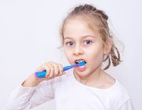 Child girl in pyjamas brushing teeth - bedtime hygiene. Close up portrait of five years old caucasian blond child girl in pyjamas brushing teeth on a white Stock Photography