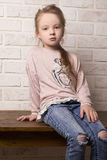 Child Girl in ragged jeans and sneakers Stock Image