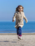 Child girl in raincoat running on beach Royalty Free Stock Photo
