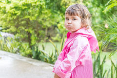 Child girl in raincoat under rain drops, outdoor portrait Royalty Free Stock Images