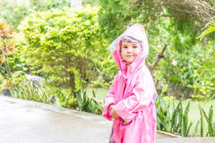 Child girl in raincoat under rain drops, outdoor portrait Stock Images