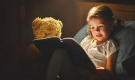Child girl reading a book in bed Royalty Free Stock Images