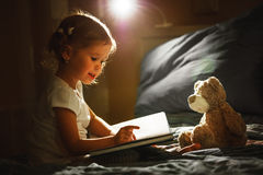 Child girl reading a book in bed. Before going to sleep Royalty Free Stock Image