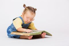Child girl reading book. Pretty girl sitting with book and reading over white Stock Images