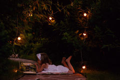 Child girl reading book in evening summer garden with lights decorations Royalty Free Stock Images
