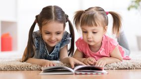 Child girl reading book with little sister at home royalty free stock photography