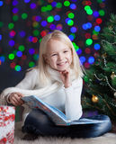 Child girl reading book near Christmas tree Stock Images