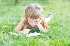 Child girl reading book outdoors on natural background. Young child girl reading book outdoors on natural background Stock Image