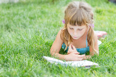 child girl reading book outdoors on natural background Royalty Free Stock Image