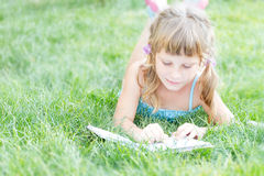child girl reading book outdoors on natural background Stock Photography