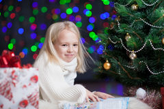 Child girl reading book under Christmas tree Stock Photos