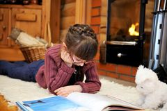 Child girl is reading in front of fireplace Royalty Free Stock Images